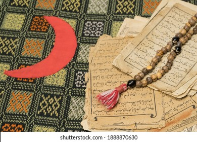 Tashkent, Uzbekistan – April 26, 2020: Muslim prayer beads with ancient pages from the Koran. Islamic and Muslim concepts. Ancient old sheets of paper from the Arabic book