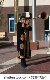 TASHKENT UZBEKISTAN - December 9 2011: Musician men in traditional kaftans playing the karnay at the entrance
