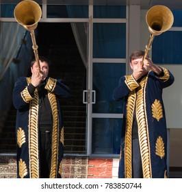 TASHKENT, UZBEKISTAN - December 9, 2011: Two musician men in traditional kaftans playing the karnay at the entrance