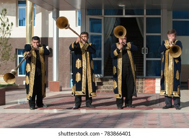 TASHKENT, UZBEKISTAN - December 9, 2011: Musician men in traditional kaftans playing the karnay at the entrance