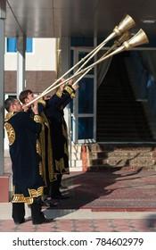 TASHKENT, UZBEKISTAN - December 9, 2011: Musician men in traditional kaftans playing the karnay at the entrance