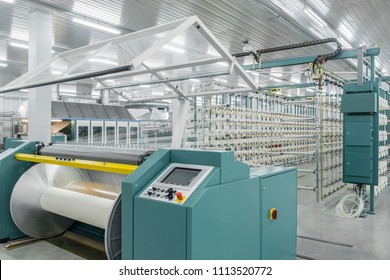 Tashkent, Uzbekistan - February 24, 2018: textile factory. textile yarn on the wrapping machine is screwed on the big shaft. machinery and equipment.