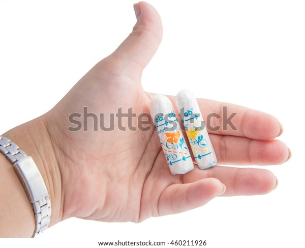 Tashkent, Uzbekistan - July 20, 2016: woman's hand holding a clean cotton tampon O.B. on white background and one can see defference between tampon sizes