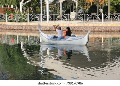 TASHKENT, UZBEKISTAN, OCTOBER 14, 2017: Young happy family in love in a boat. Outdoors portrait