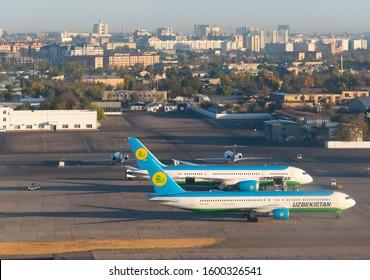 Tashkent / Uzbekistan - October 17 2019: Aerial view of two Uzbekistan Airways aircraft at Islam Karimov Tashkent International Airport with the city skyline in background. Uzbek airline from Asia.