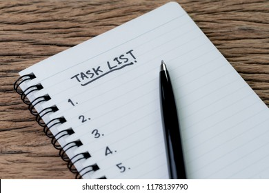 Task List, project management concept, pen on white paper notepad with handwritten headline as Task List and numbers listed on wood table, writing business project with tasks prioritize.