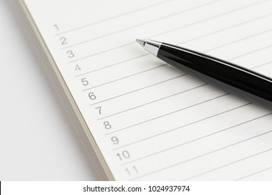 Task list or shopping wish list concept by closed up of black pen on white note pad with list of numbers from 1 to 10 in soft tone.