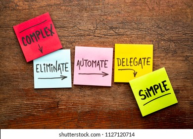 Task management concept from complexity to simplicity: eliminate, automate, delegate. Handwriting on sticky notes against rustic wood board.