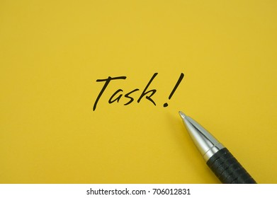 Task! note with pen on yellow background