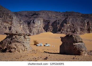 TASSILI N'AJJER, ALGERIA - JANUARY 10, 2002: unknown men with their off-road vehicles in the sand dunes of the Algerian Sahara desert, Africa, Tassili N'Ajjer National Park