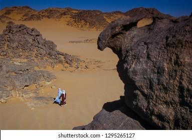 TASSILI N'AJJER, ALGERIA - JANUARY 10, 2002: two unknown men walks in the sand dunes of the Algerian Sahara desert, Africa, Tassili N'Ajjer National Park