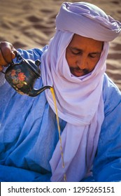TASSILI N'AJJER, ALGERIA - JANUARY 10, 2002: unknown man during the mint tea ritual in the sand dunes of the Algerian Sahara desert, Africa, Tassili N'Ajjer National Park