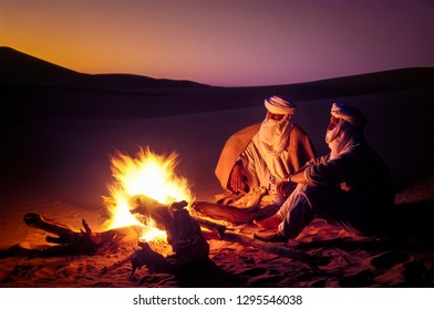 TASSILI N'AJJER, ALGERIA - JANUARY 10, 2002: unknown men at sunset with fire in the sand dunes of the Algerian Sahara desert, Africa, Tassili N'Ajjer National Park
