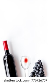 Taste red wine. Bottle of red wine, glass and black grape on white background top view copyspace