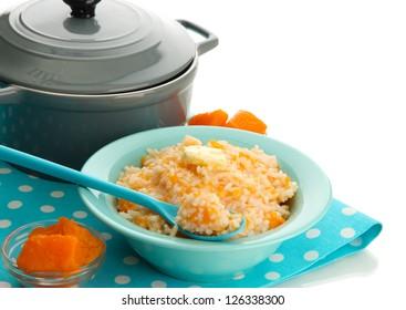 Taste rice porridge with pumpkin in blue bowl, isolated on white