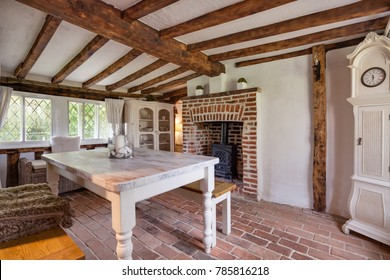 Tastefully modernised dining room withing 16th Century English cottage with traditionally styled decor sympathetic to the original period with dining table and bench stool, cast iron stove.