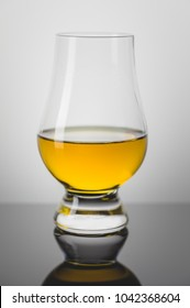 Taster Glass with a Dram of Scotch Whisky on Black Mirror.