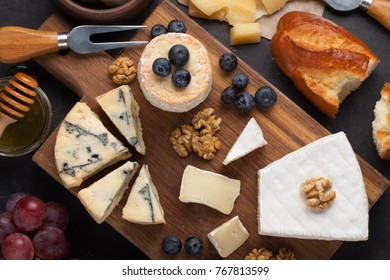 Tasting cheese dish on a dark stone plate. Food for wine and romantic date, cheese delicatessen on a black concrete background. Top view.