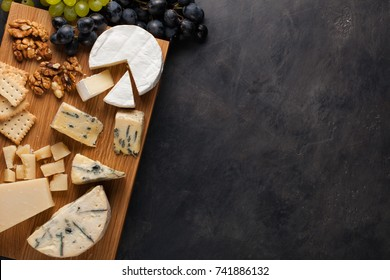 Tasting cheese dish on a wooden plate. Food for wine and romantic, cheese delicatessen on a dark stone table. Top view with copy space.