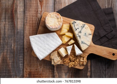 Tasting cheese dish on a wooden plate. Food for wine and romantic, cheese delicatessen on a wooden rustic table. Top view with copy space.
