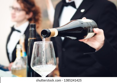 Tasting experience with a sommelier serving a glass of Moscato d'Asti (Muscat) sparkling wine in Alba (Piedmont, Italy)