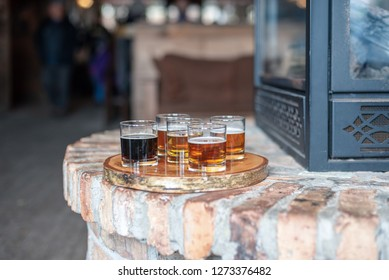 Tasting glasses of beer on rustic serving tray by the fire at local microbrewery