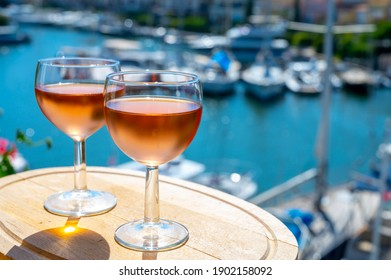 Tasting of local cold rose wine in summer with sail boats haven of Port grimaud on background, Provence, Var, France