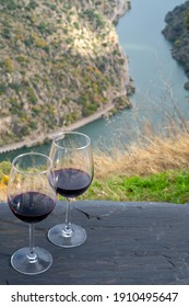 Tasting of Portuguese red dry wine, produced in Douro Valley and Douro river and terraced vineyards on background in autumn, North of Portugal
