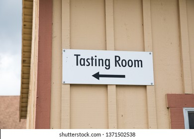 Tasting room sign with an arrow pointing to the wine tasting room at a large winery estate in the Russian River Valley of California.