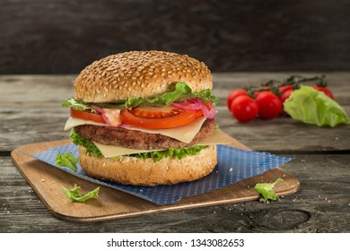 Tasty and appetising cheeseburger with tomato and green salad served on the wooden table