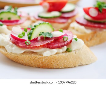 Tasty appetizer, slices of brad with salami, cheese, red radish cucumbers and spring scallions on a marble tile.