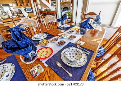 Tasty appetizers, cheese, nuts, crackers, served on blue and white dishes.