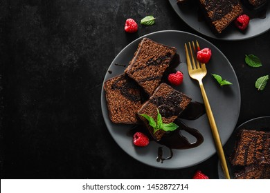 Tasty appetizing chocolate cake served with chocolate sauce and mint on plate with fork. Ready for eating.  Dark background.