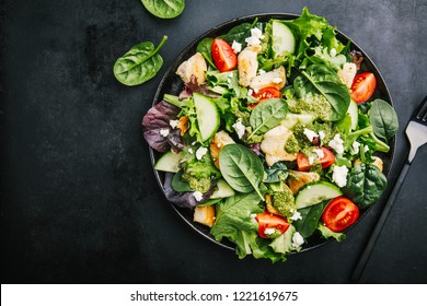 Tasty appetizing fresh salad with chicken, tomatoes, cucumbers, pesto sauce and cheese feta in bowl on black background. View from above. Horizontal with copy space.