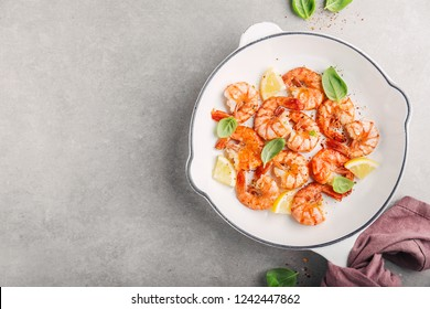 Tasty appetizing fried grilled shrimps with spices on white pan. View from above with copy space.
