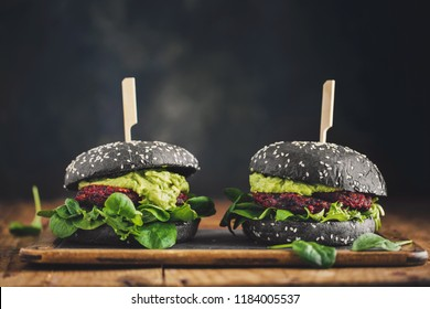 Tasty appetizing healthy vegan black burgers with beetroot, quinoa and avocado sauce served on wooden table. Horizontal with copy space. Concept of healthy food, clean eating