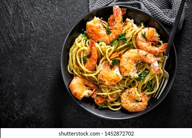 Tasty appetizing pasta spaghetti with pesto sauce and shrimps served in bowl on dark background. Top View with Copy Space.