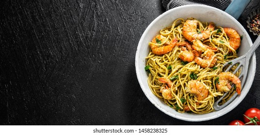 Tasty appetizing pasta spaghetti with pesto sauce and shrimps served on pan on dark background. Top View with Copy Space. Banner