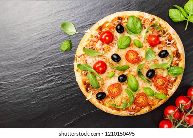 Tasty appetizing pizza with cheese, tomatoes, arugula, olives, basil on dark stone background. View from above with copy space.