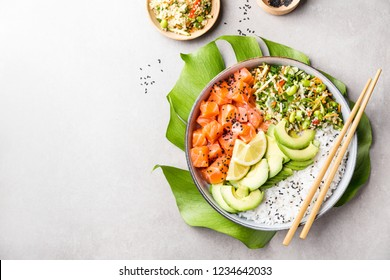 Tasty appetizing poke bowl served with salmon, avocado, rice, salad with edamame. Grey background. View from above with copy space.