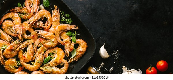 Tasty appetizing roasted shrimps prawns with spices on pan with ingredients on black background. Top View with Copy space. Food Background Italian Kitchen Concept