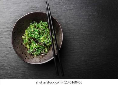 Tasty appetizing seaweed salad on dark plate on slate background. Closeup