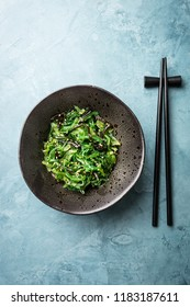 Tasty appetizing seaweed salad on plate on table. Top View with Copy Space