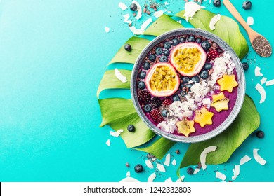 Tasty appetizing smoothie acai bowl made from blackberries and wild berries, decorated with cut passion fruit, coconut flakes, and cacao nibs. Served in bowl. Healthy life clean eating concept.