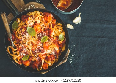 Tasty appetizing spaghetti with tomato sauce and cheese on pan on table. View from above. Horizontal with copy space.