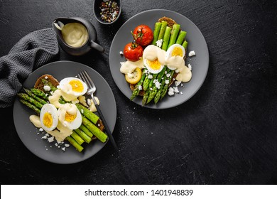 Tasty appetizing toasts with asparagus, eggs, cheese and sauce hollandaise served on plates on dark background. View from above with copy space.