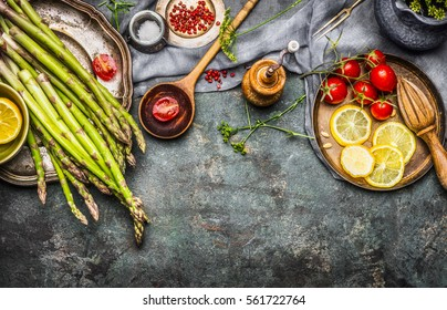 Tasty asparagus cooking with tomatoes, lemon and seasoning, preparation on rustic kitchen table with wooden spoon, top view, border. Dark style