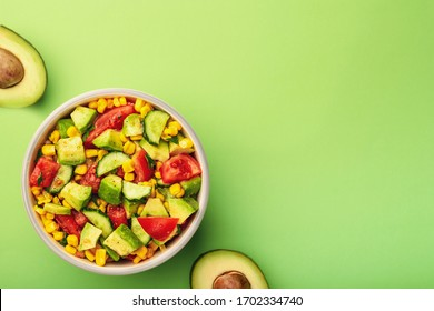 Tasty avocado salad with tomatoes, cucumbers in bowl on green background with copy space.