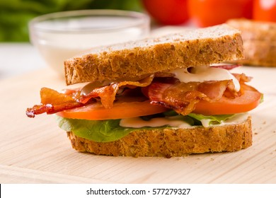 tasty bacon sandwich on wooden table with mayonnaise