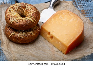 Tasty baked bagels with melted cheese and piece of aged Dutch Gouda cheese close up